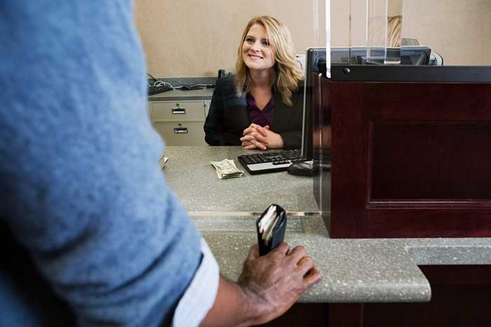 A customer speaking with a bank teller sitting across the counter.
