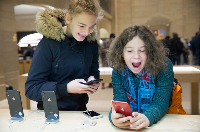 Enthusiastic children playing with display iPhones in an Apple store.